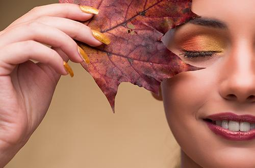 Woman holding a maple leaf to her face.