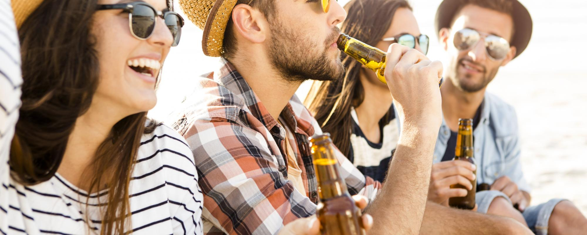 Young adults drinking beer outside in summer