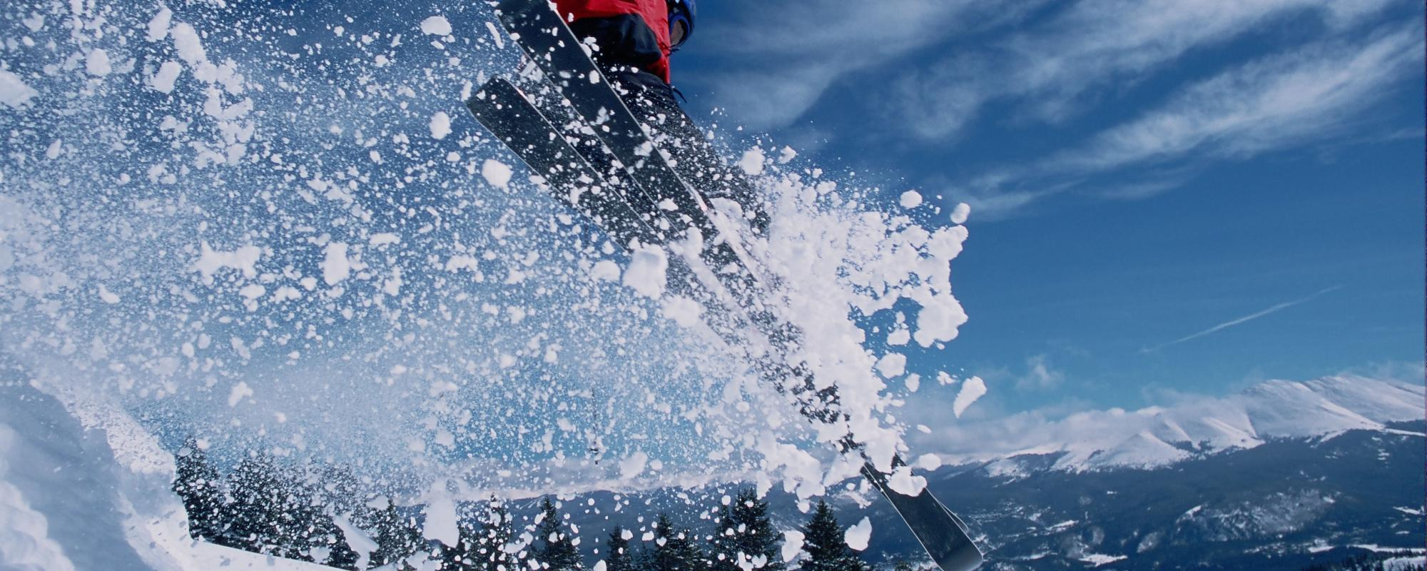 Skiier jumping in the snow covered mountains
