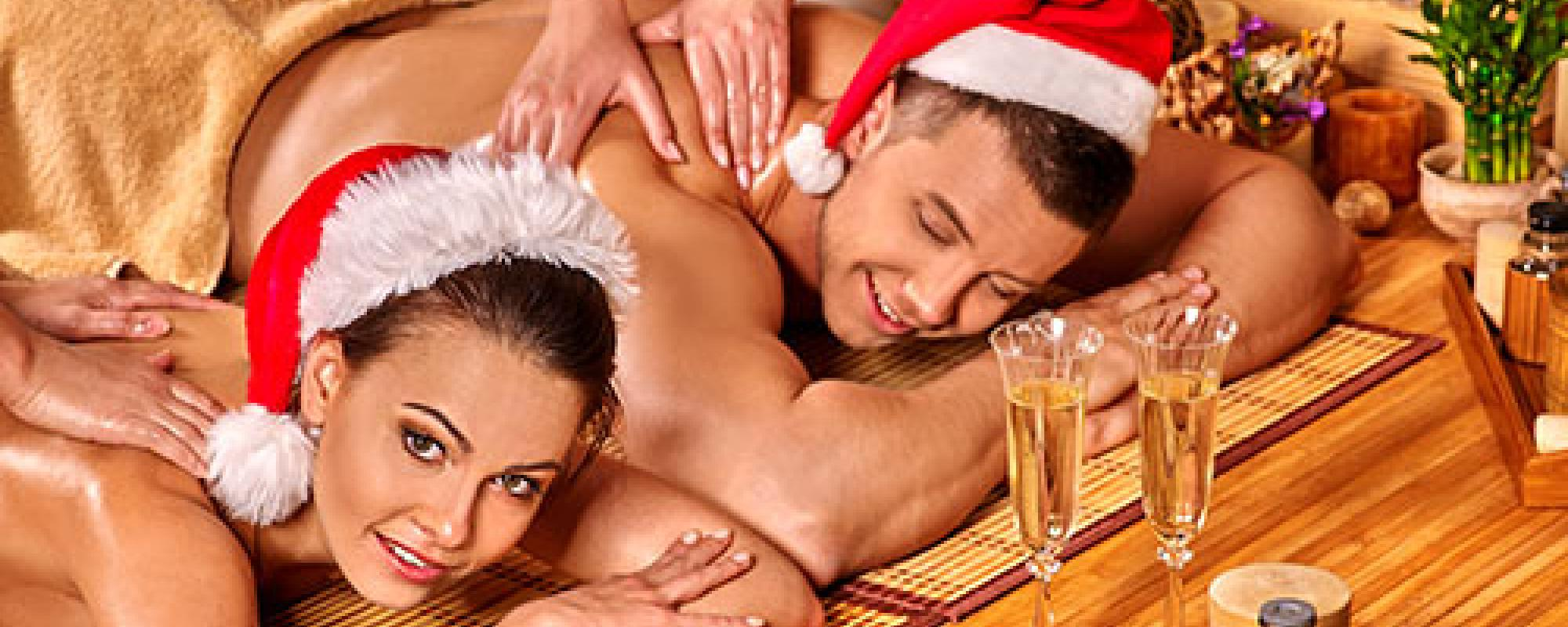 A couple in Santa hats getting a holiday massage.