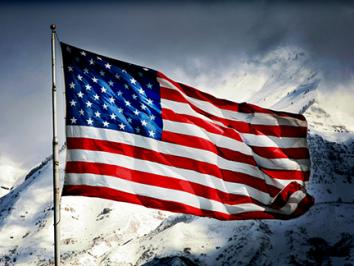 American flag flying in front of mountains.