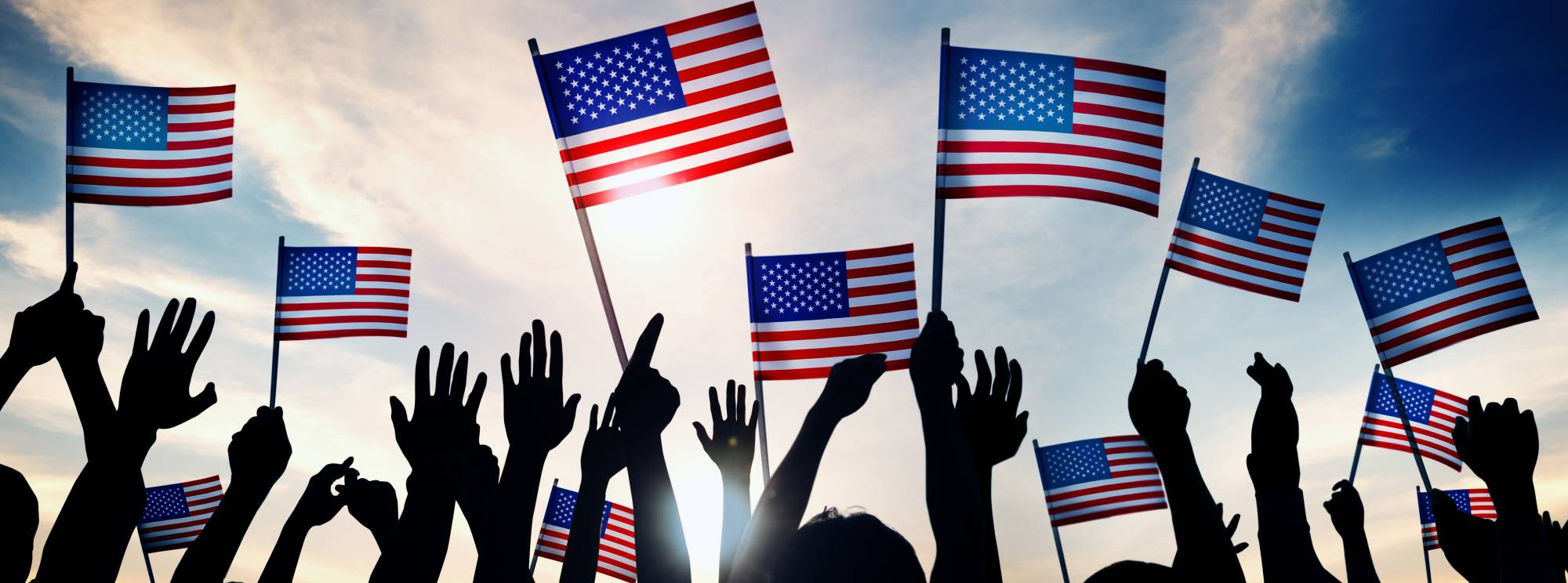american flags being waved in the sun